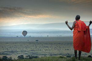 Masai man watching a hot-air balloon over the savannah