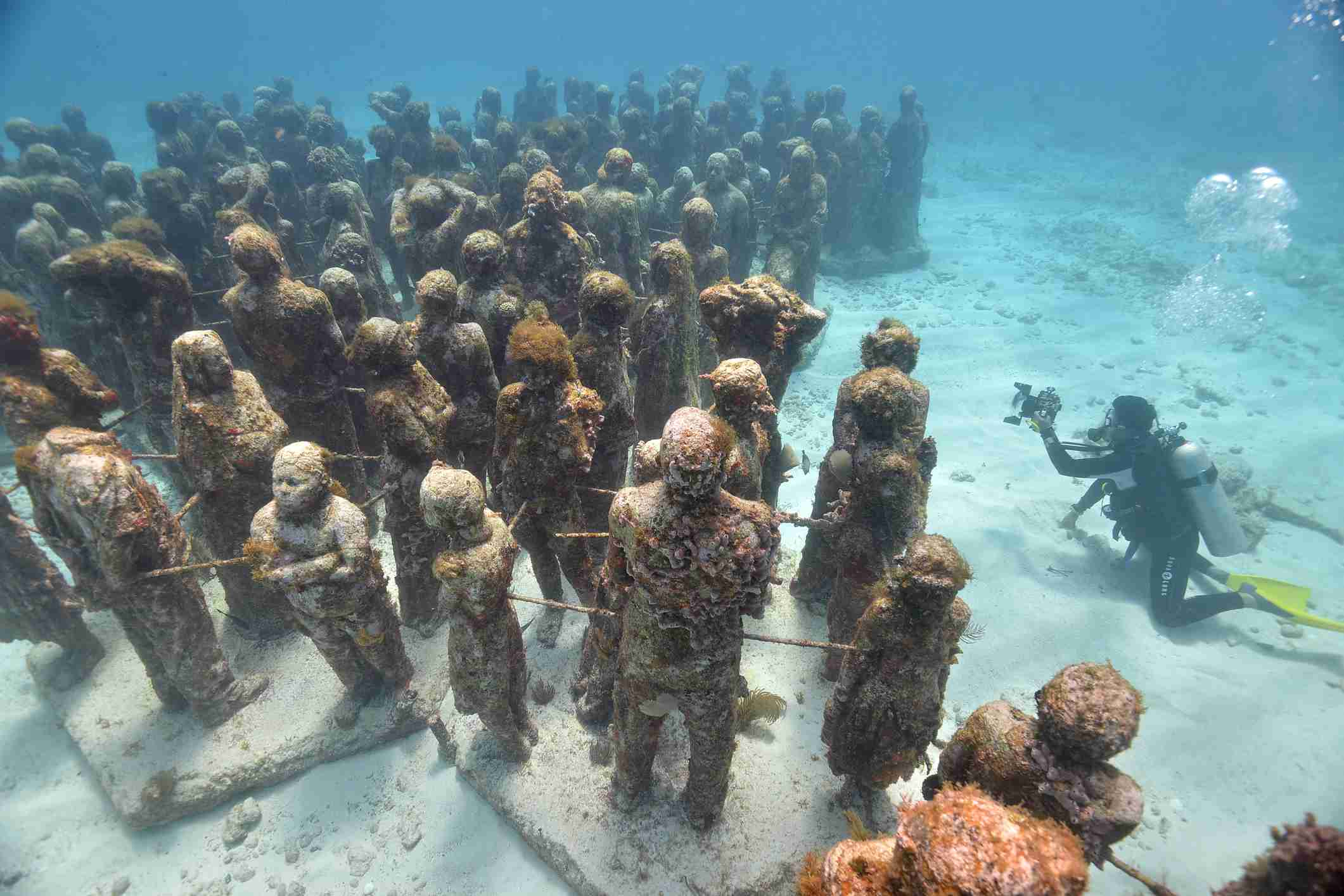 High angle view scuba diver photographing Cancuns underwater statues, Isla Mujeres, Quintana Roo, Mexico