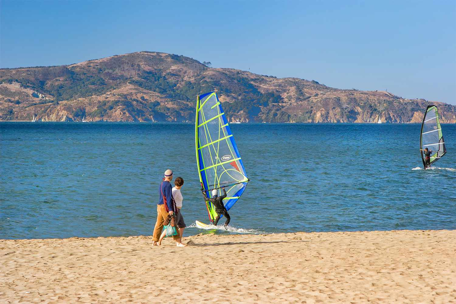 Two people walking on beach with windsurfers in water