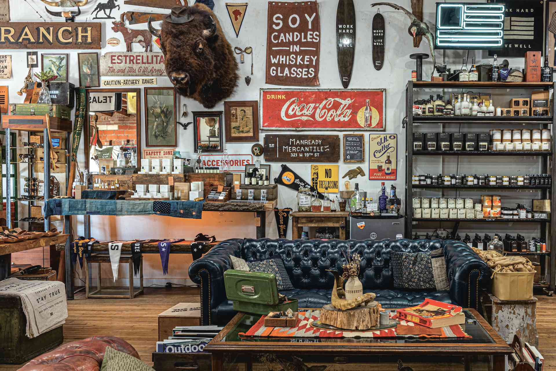 Interior of Manready Mercantile with a black leather couch, vintage signs on the walls and tables and shelves stacked with products