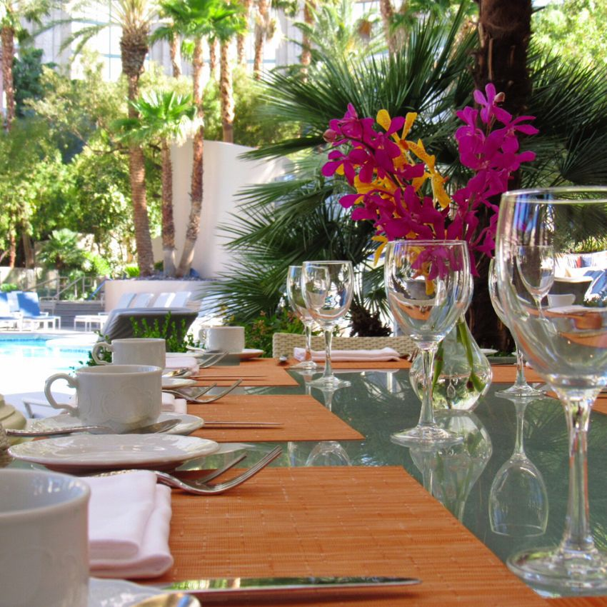 Glass table with setting surrounded by trees and flowers at the Four Seasons las Vegas