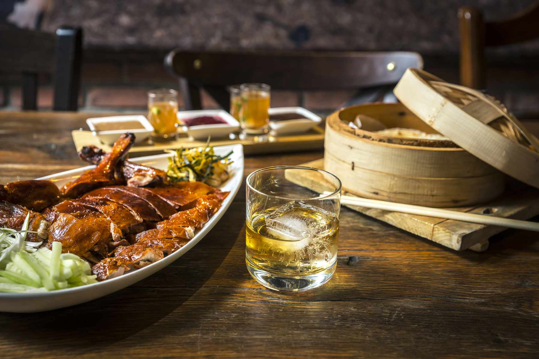 roasted duck on a table with a partially open steam basket and a glass with one ice cube at decoy