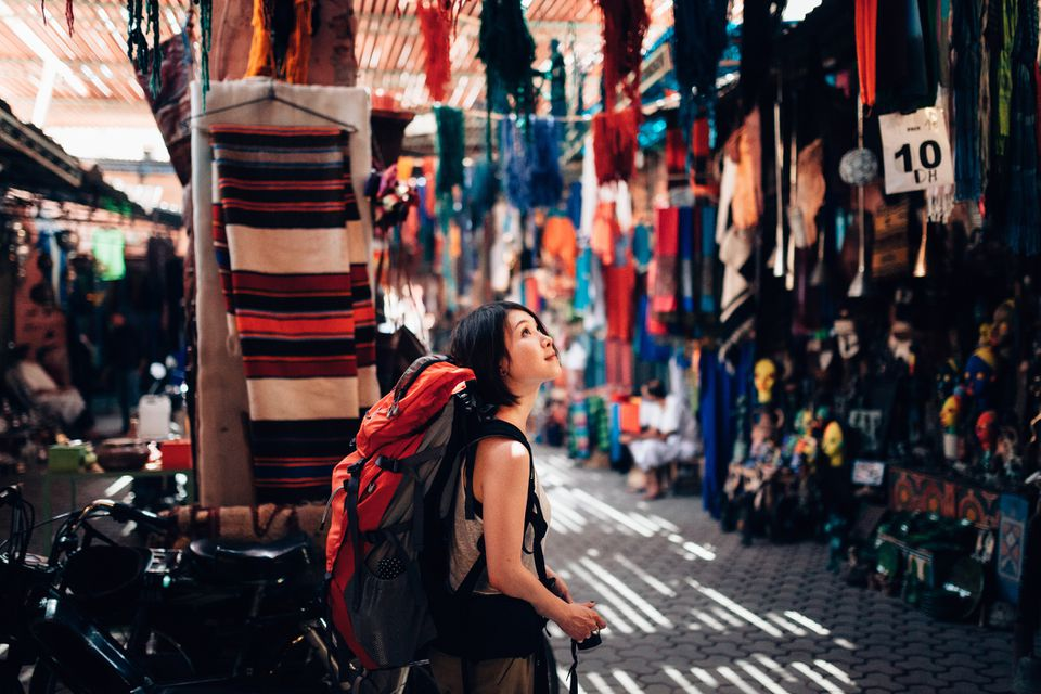 Young woman walks alone through a souk in Fez, Morocco