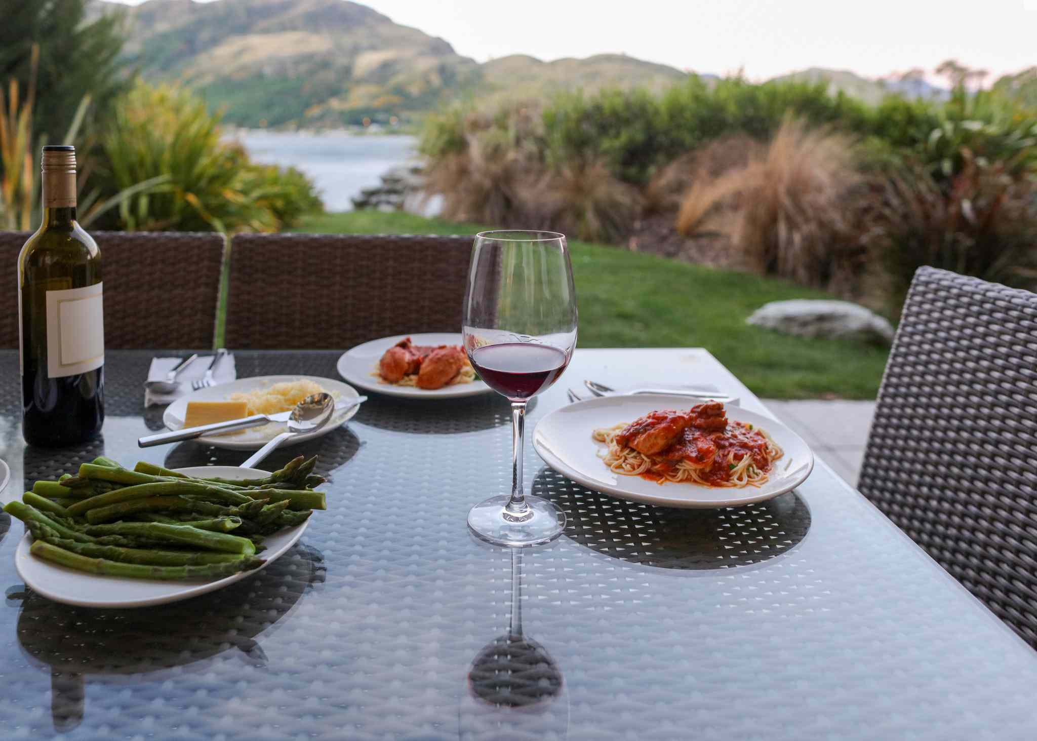 glass of wine and plates of food on an outdoor table with trees and lake in background