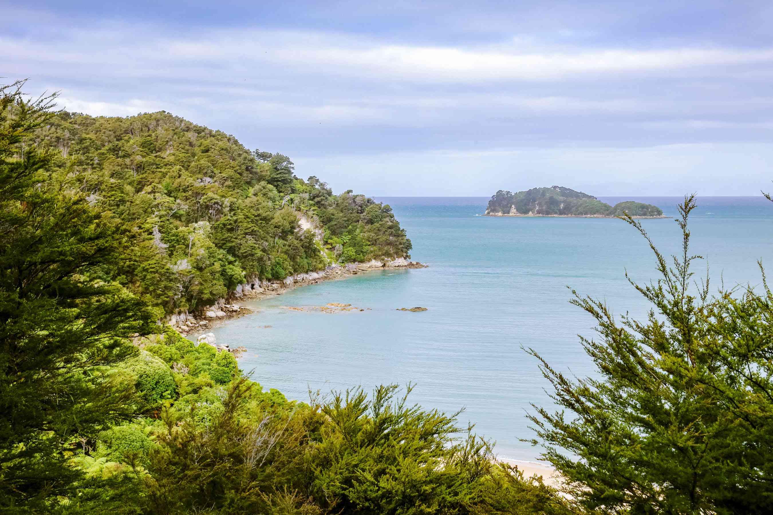 View of a blue sea on a green lush coasltine