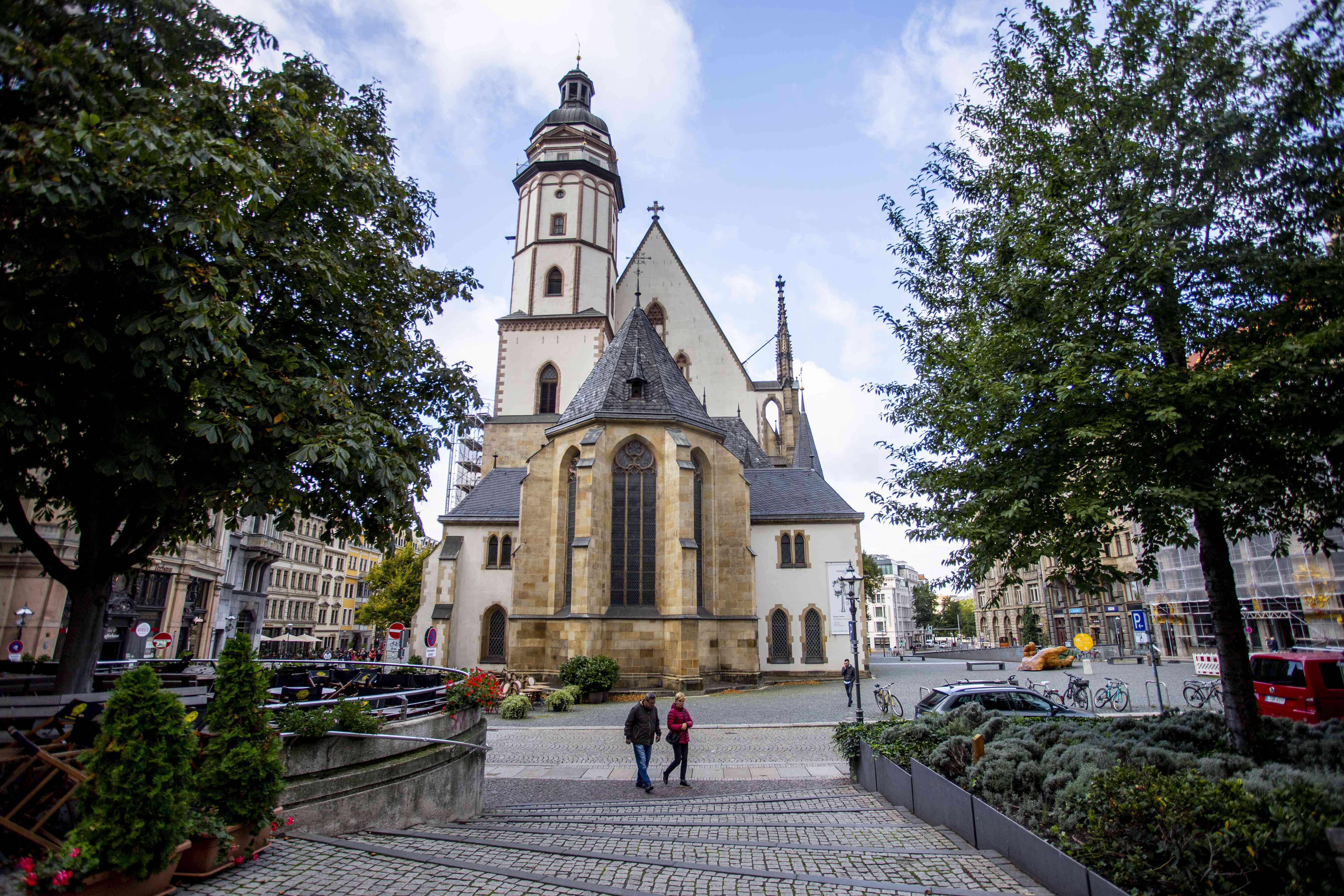 Two people walking past the front of St Thomas Church