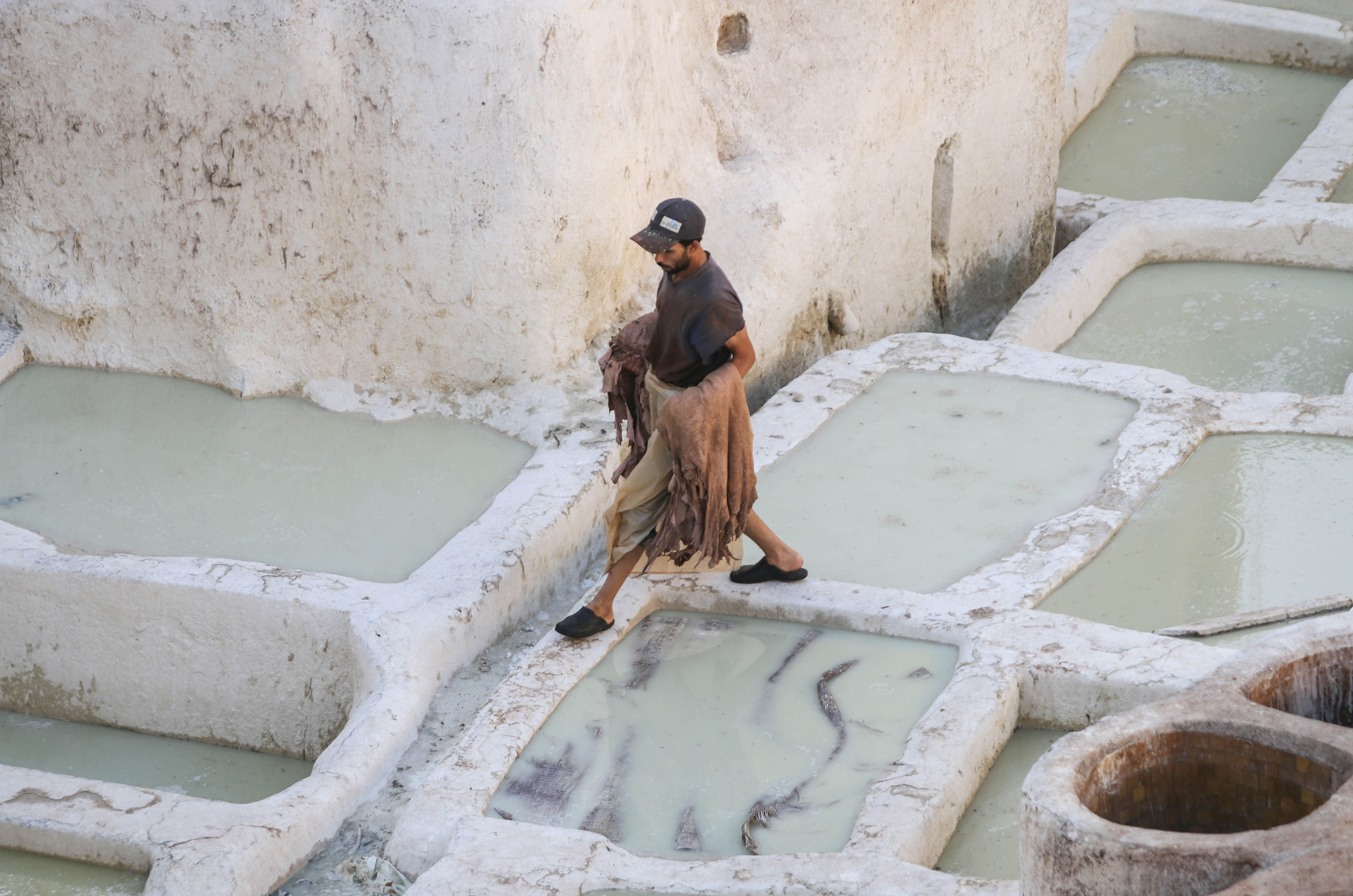 a man walking among the dye vats
