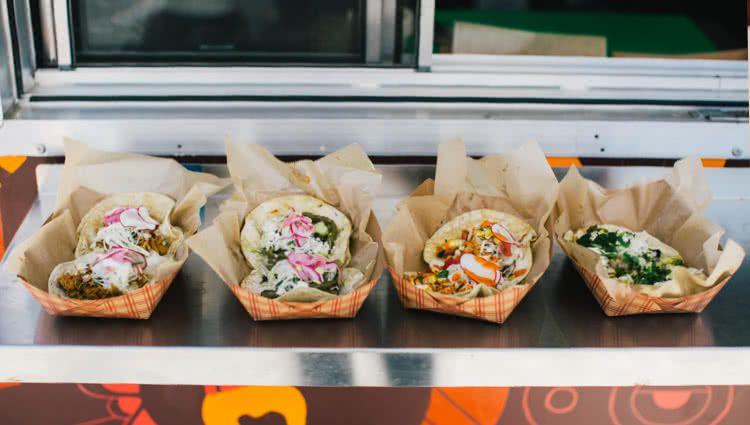 Cuatro canastas de papel con cuatro pares de tacos diferentes en la repisa de un camión de comida