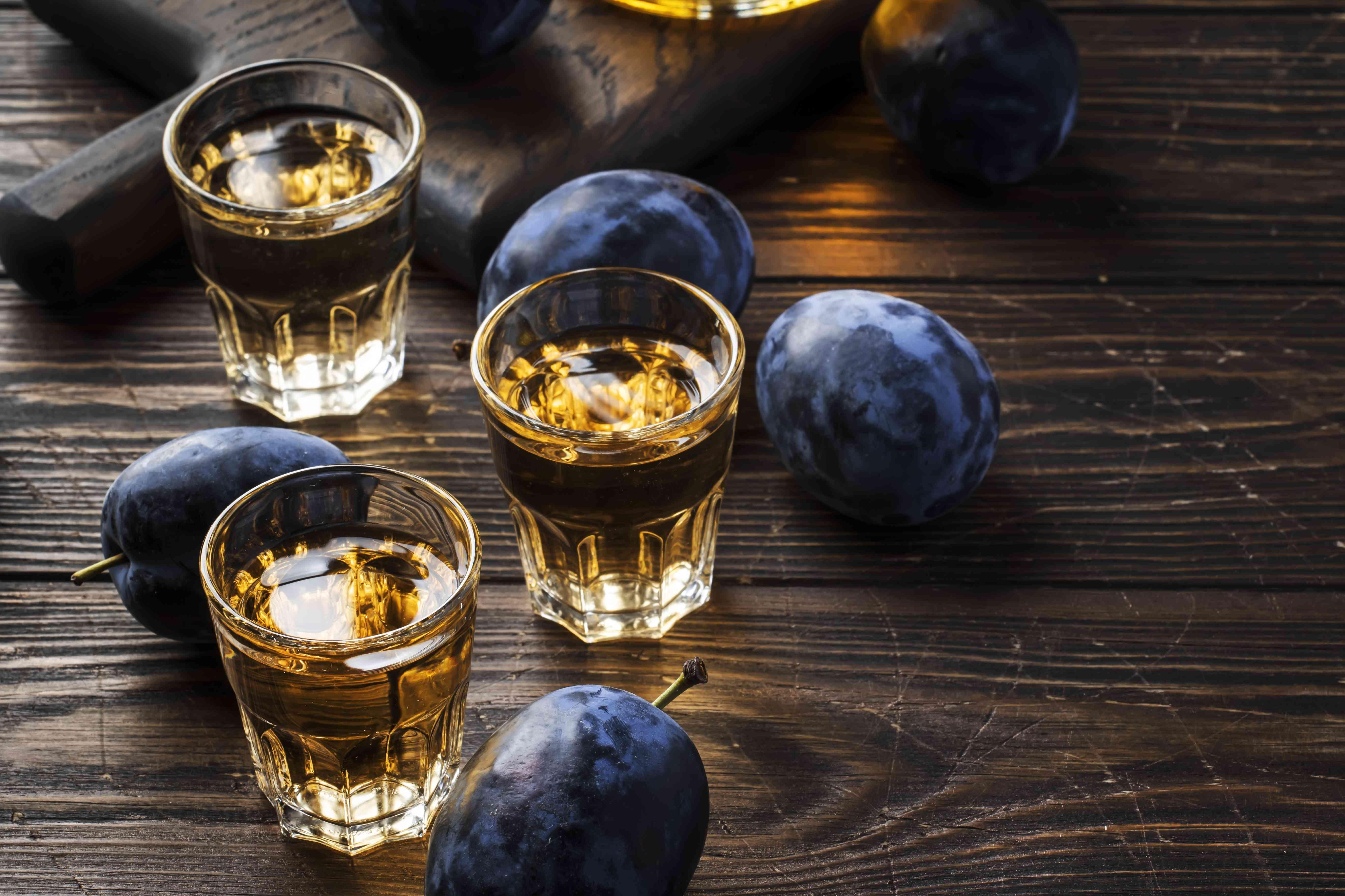 Slivovica - brandy de ciruela o vodka de ciruela, licor fuerte, bebida fuerte en vasos en una mesa de madera vieja, ciruelas frescas, espacio de copia
