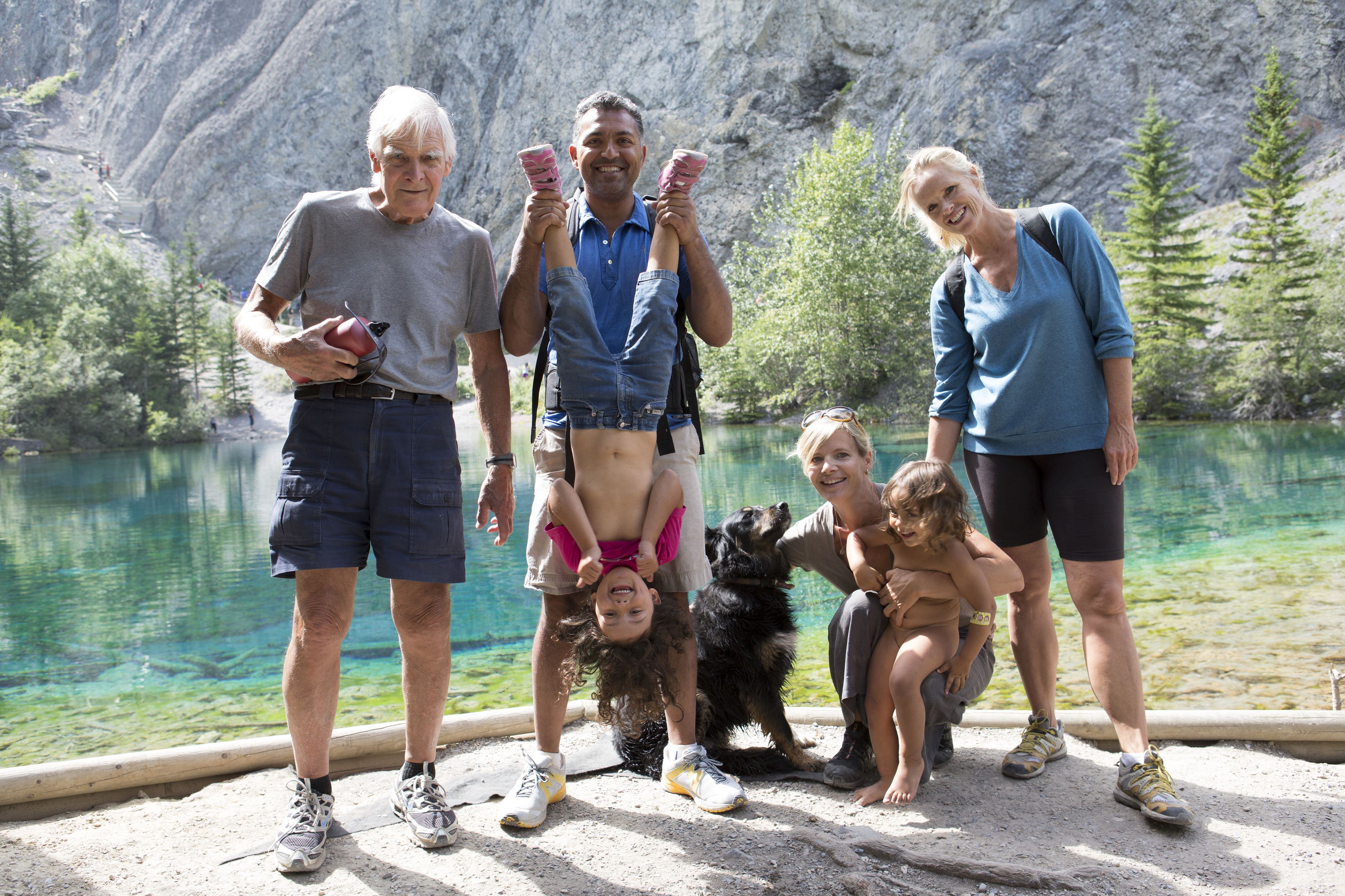 Extended family with dog pause beside mtn lake