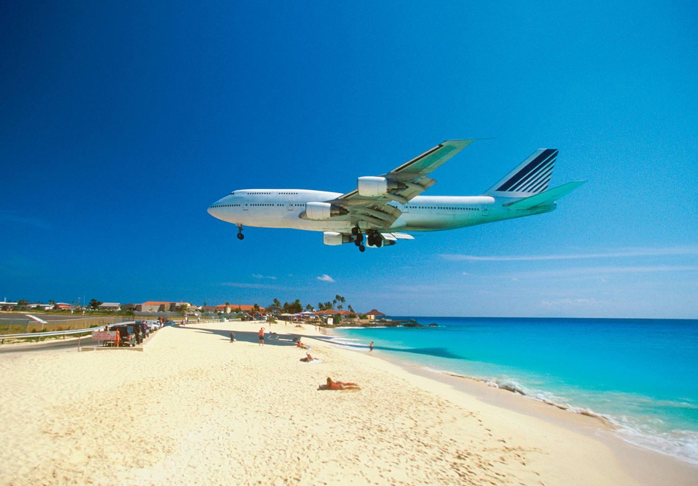 Air plane flying over a Caribean beach