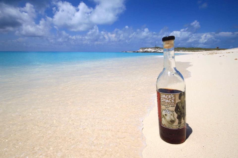 half-drunk bottle of Jack's Shack dark rum on a white sand beach