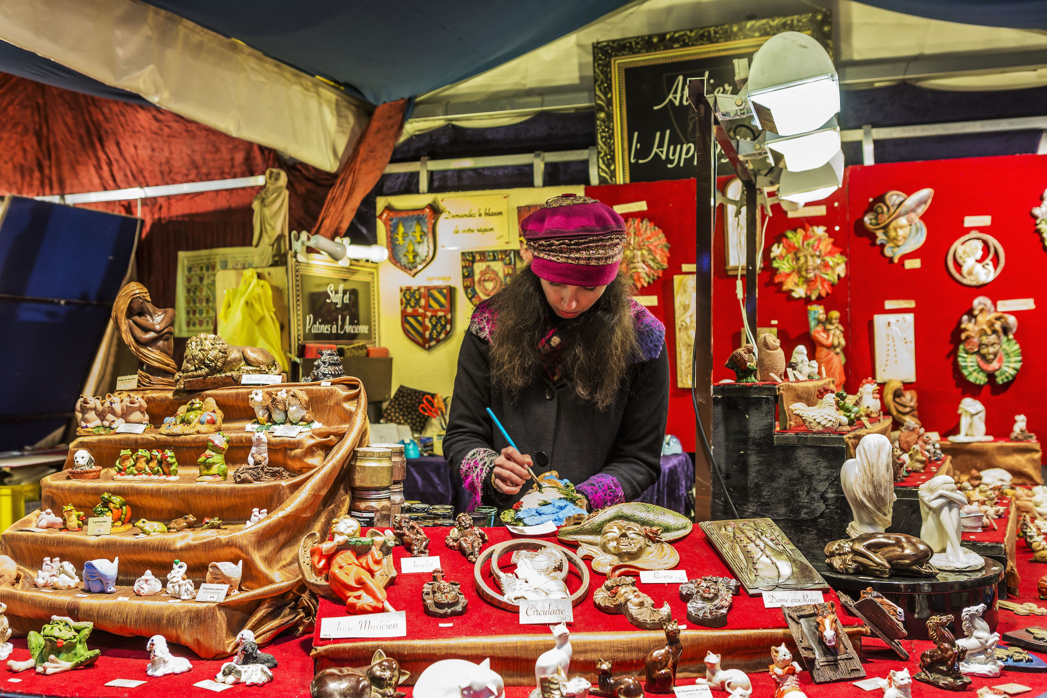 a craftswoman adds details to a ceramic piece sold at a paris christmas market stand
