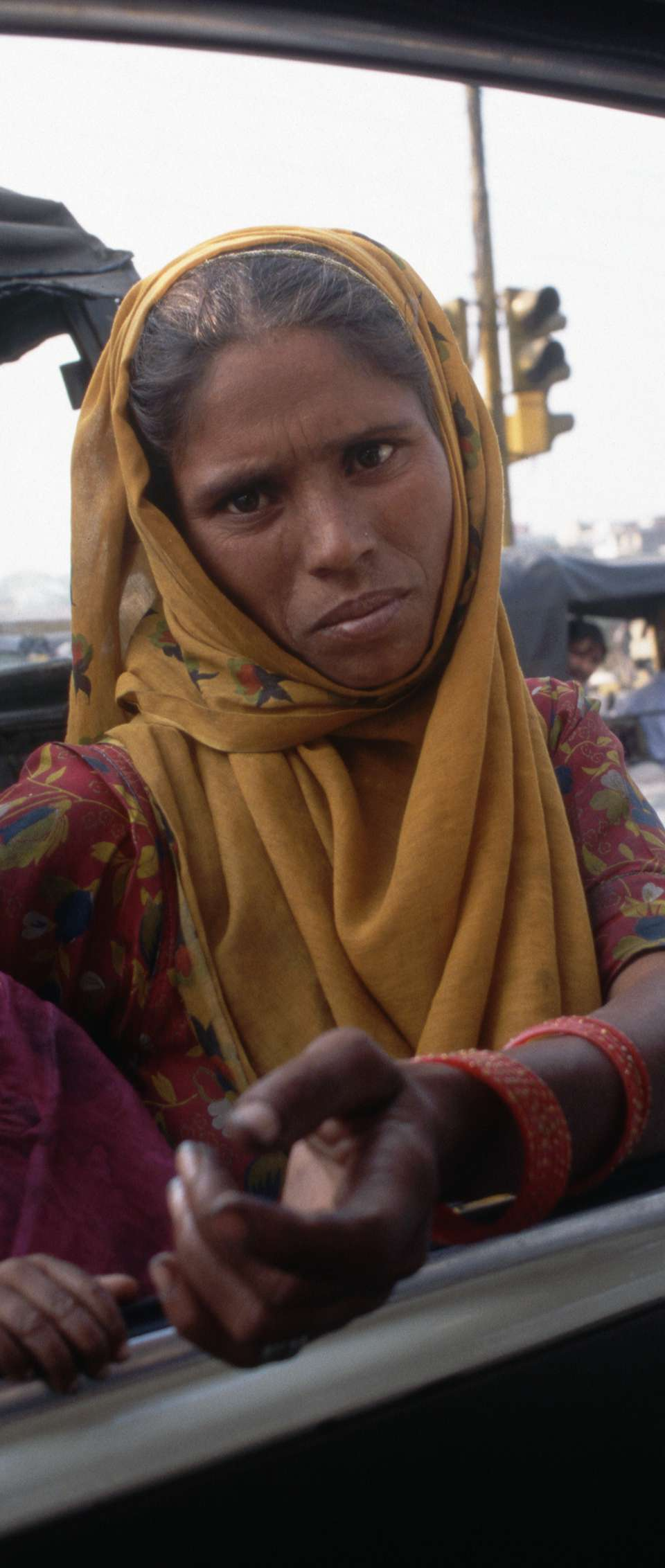 A woman carrying a young child begs for money outside a taxicab in New Delhi