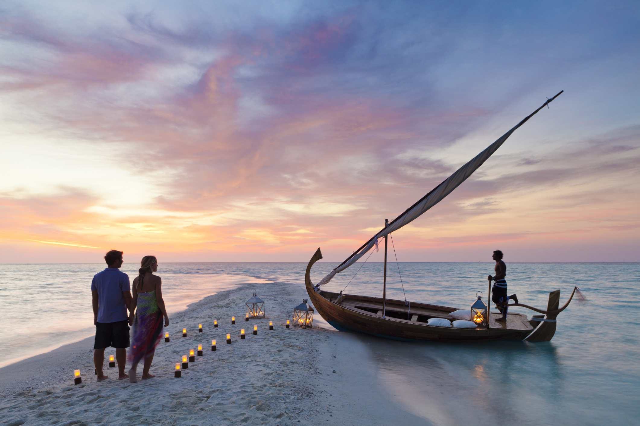 Maldives, Rasdhoo Atoll, Kuramathi Island. A couple wait to board a traditional Dhoni on the sandbank at Kuramathi Island Resort.