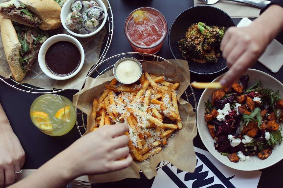 hands picking up fries out of a basket. The table has other assorted dishes on it