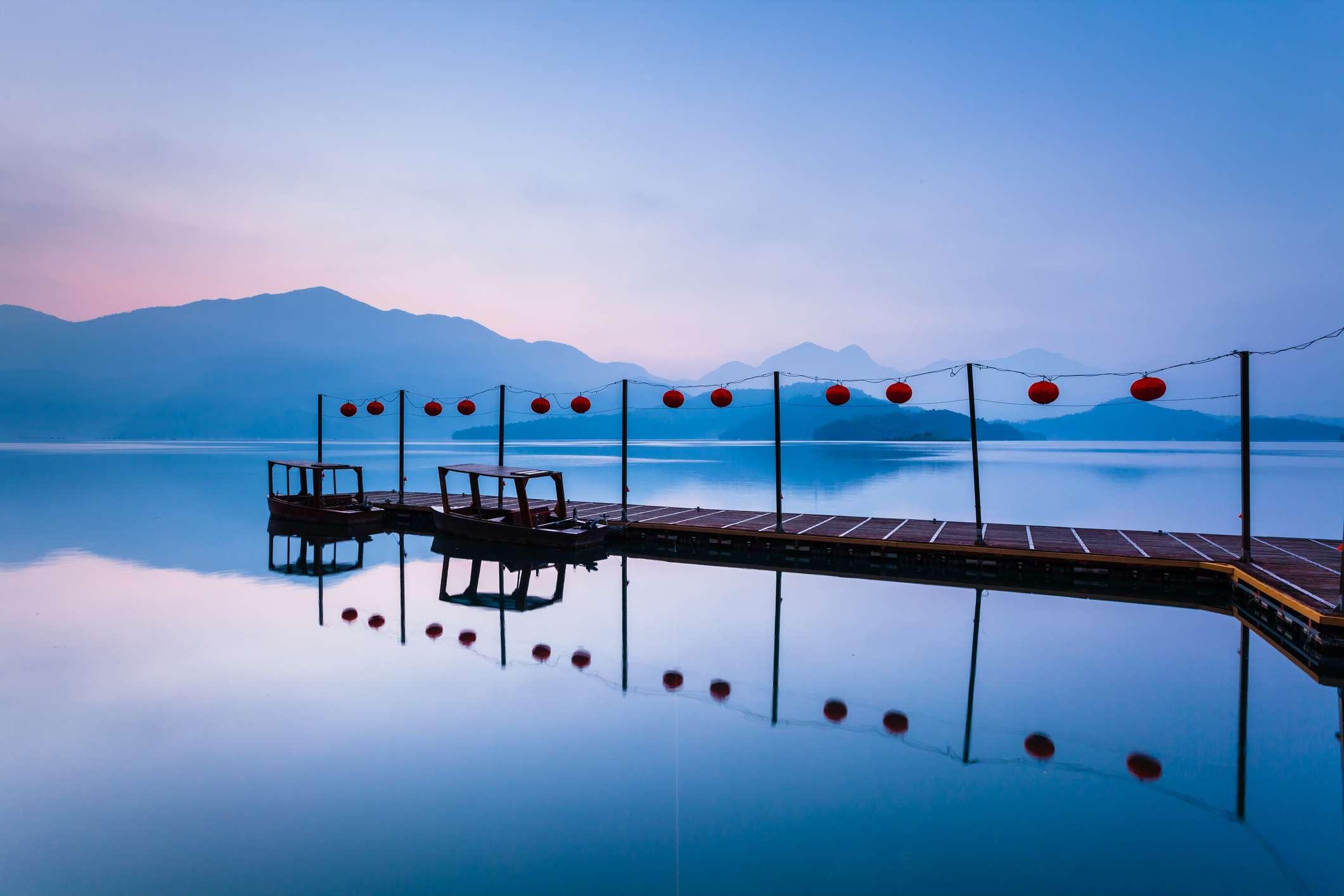 boardwalk on a calm reflective lake in taiwan