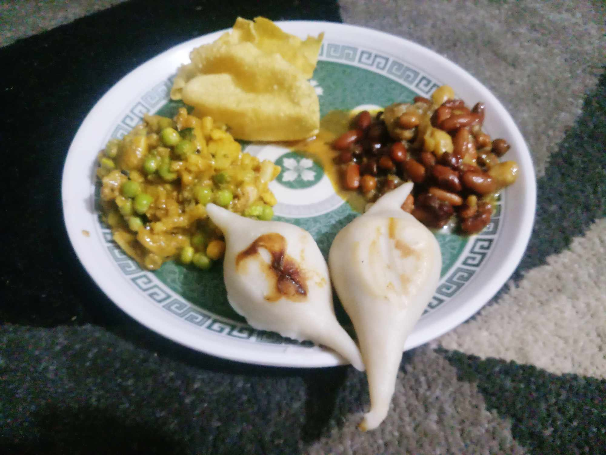 plate of various curries made with beans and peas and two white dumplings