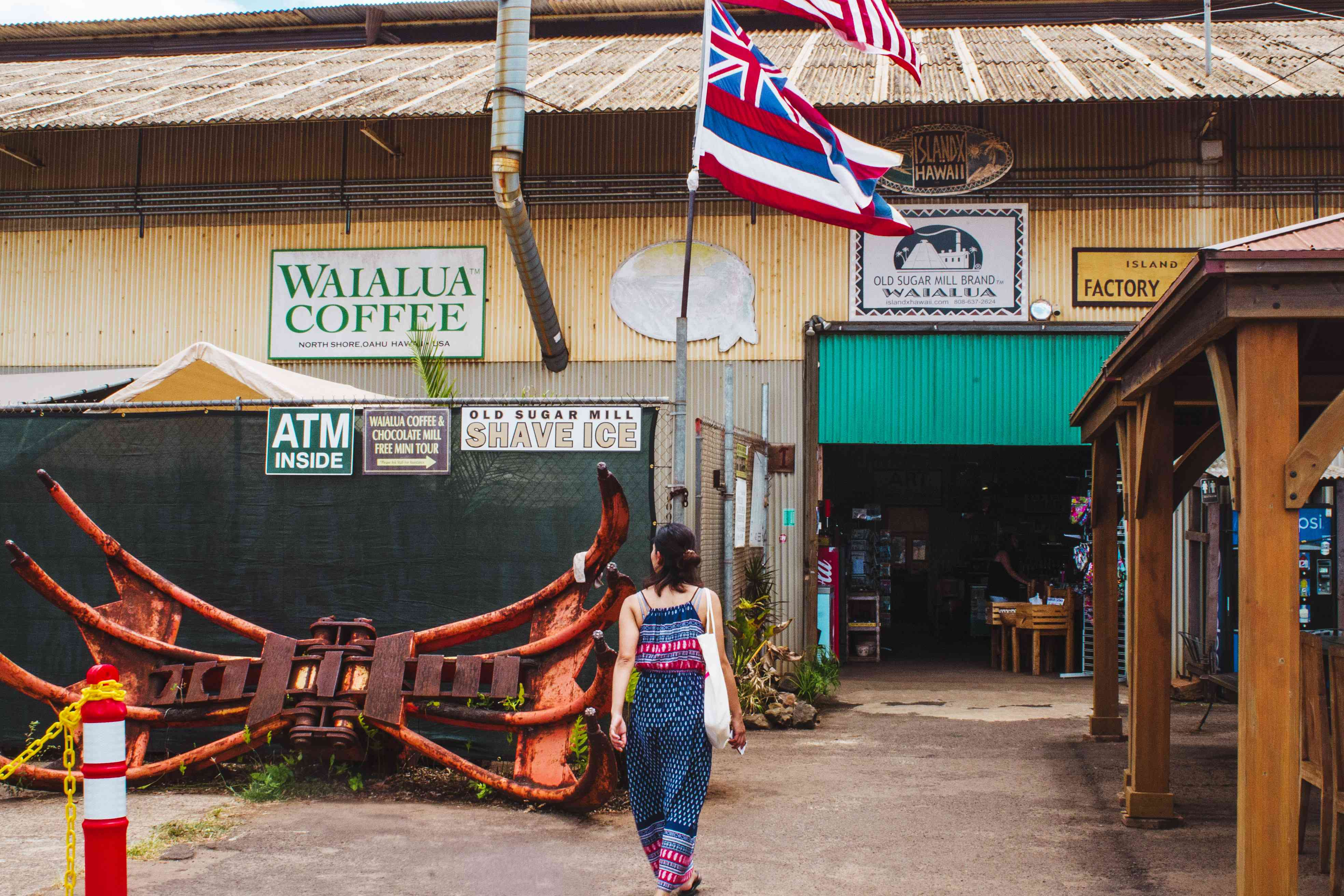 Woman entering old sugar mill that is now Waialua Coffee