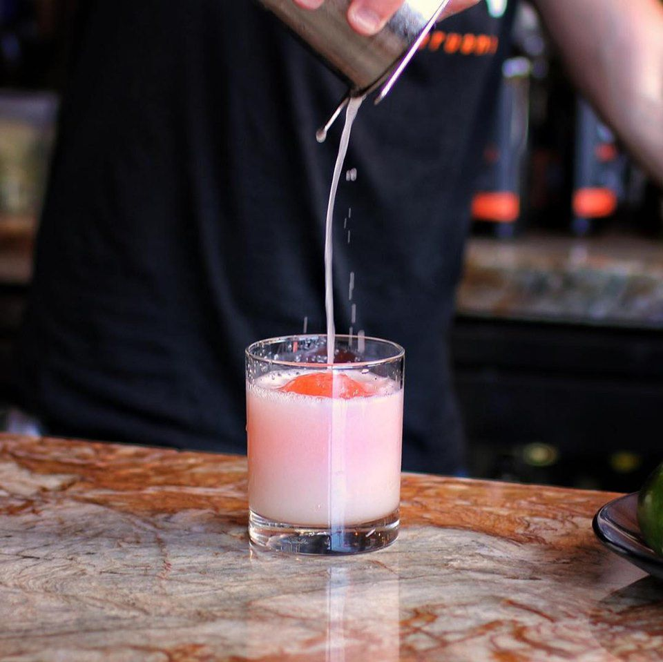 Bartender pouring a milky pink drink in to a glass from a shaker