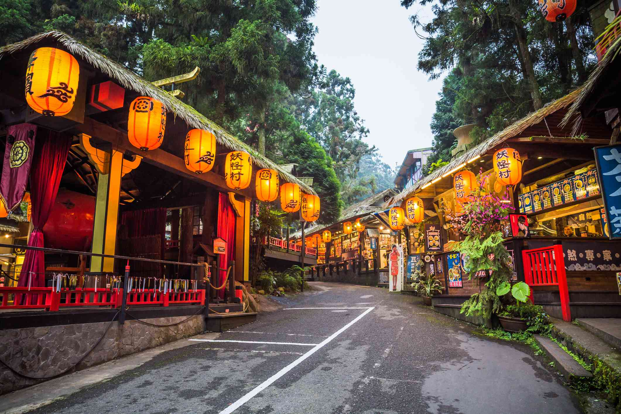 short buildings with large lanterns on an empty street in the Xitou Monster Village, Taiwan