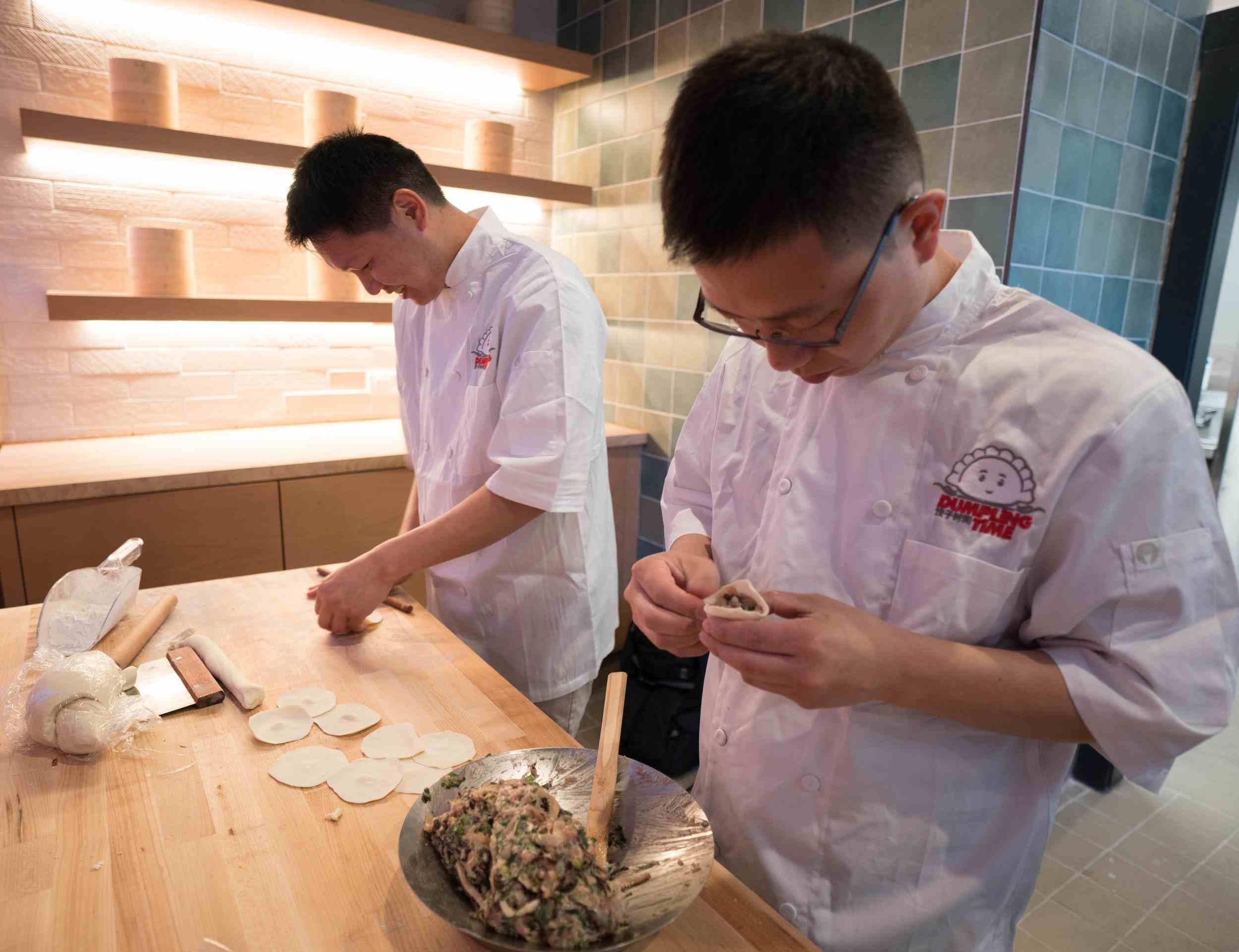 Chefs making dumplings by hand.