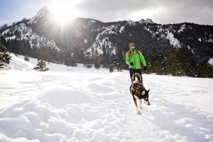 A guy and his dog hiking on a snowy trail.