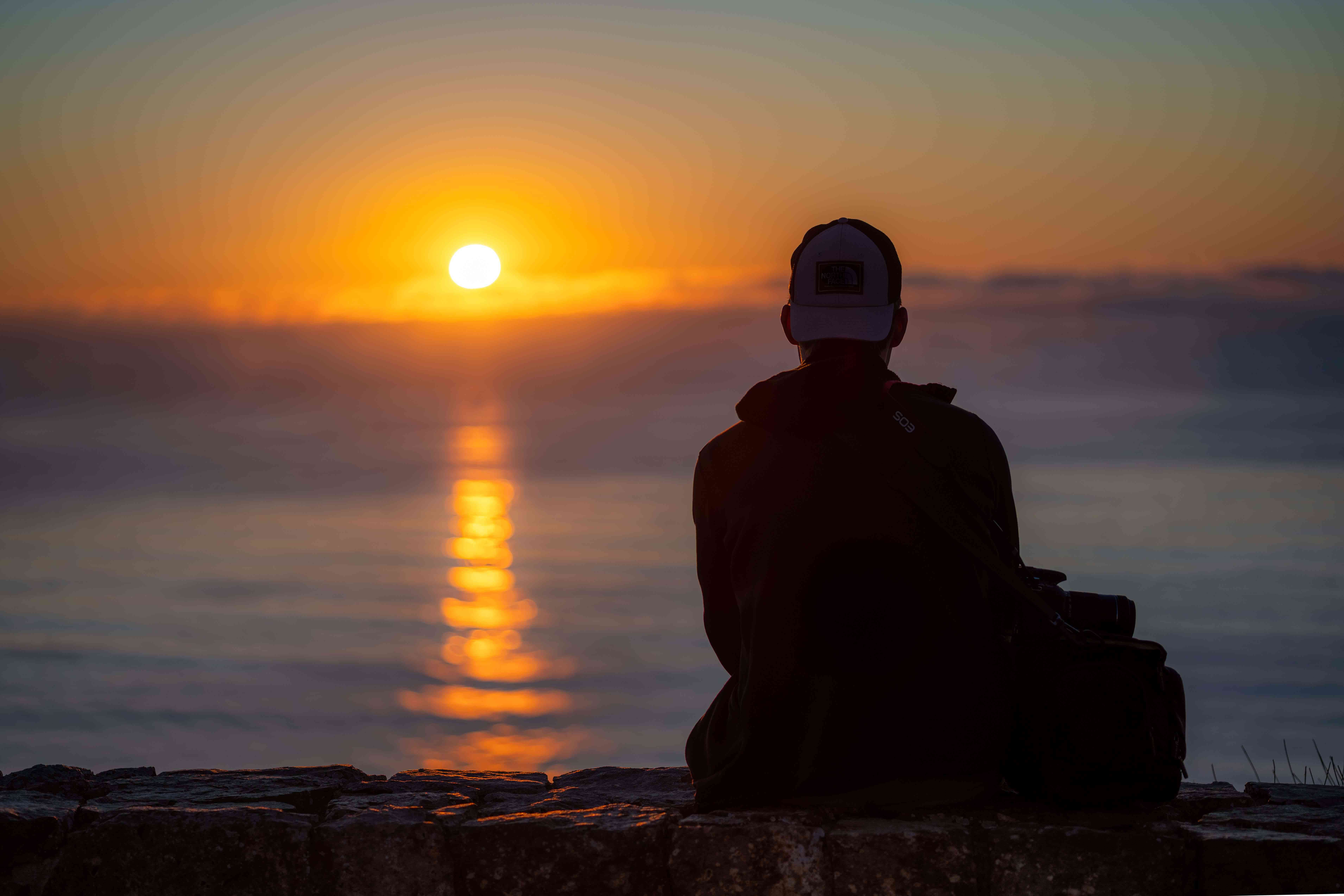 Persona sentada en el Monumento Nacional Cabrillo mirando la puesta de sol