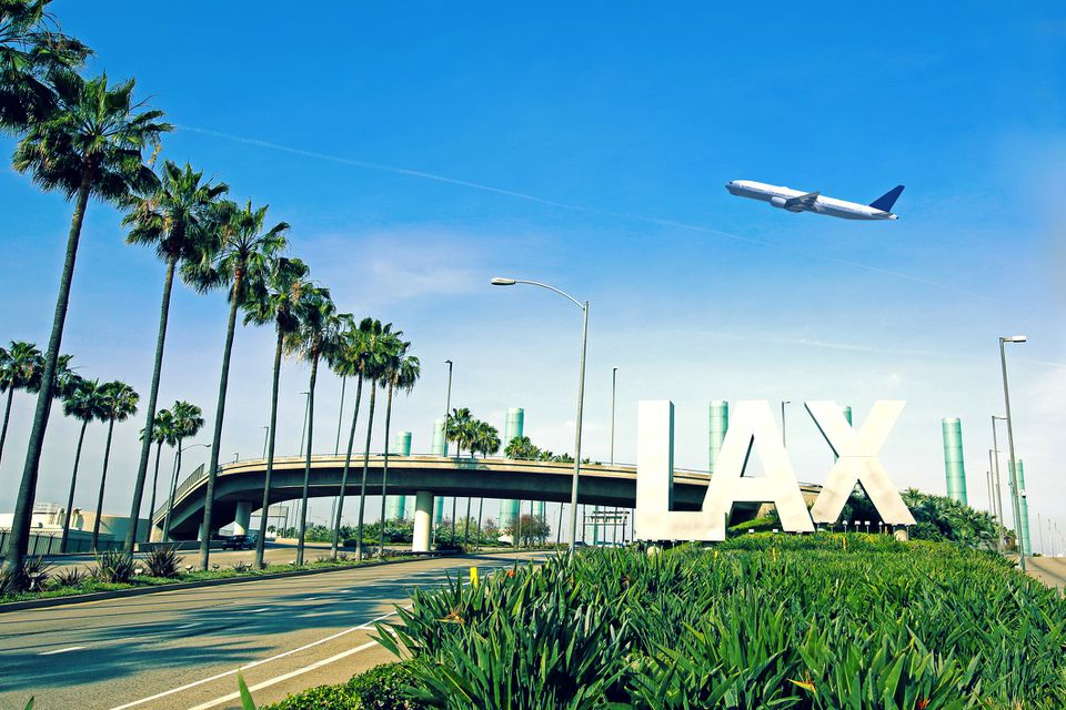 LAX sign with airplane flying overhead