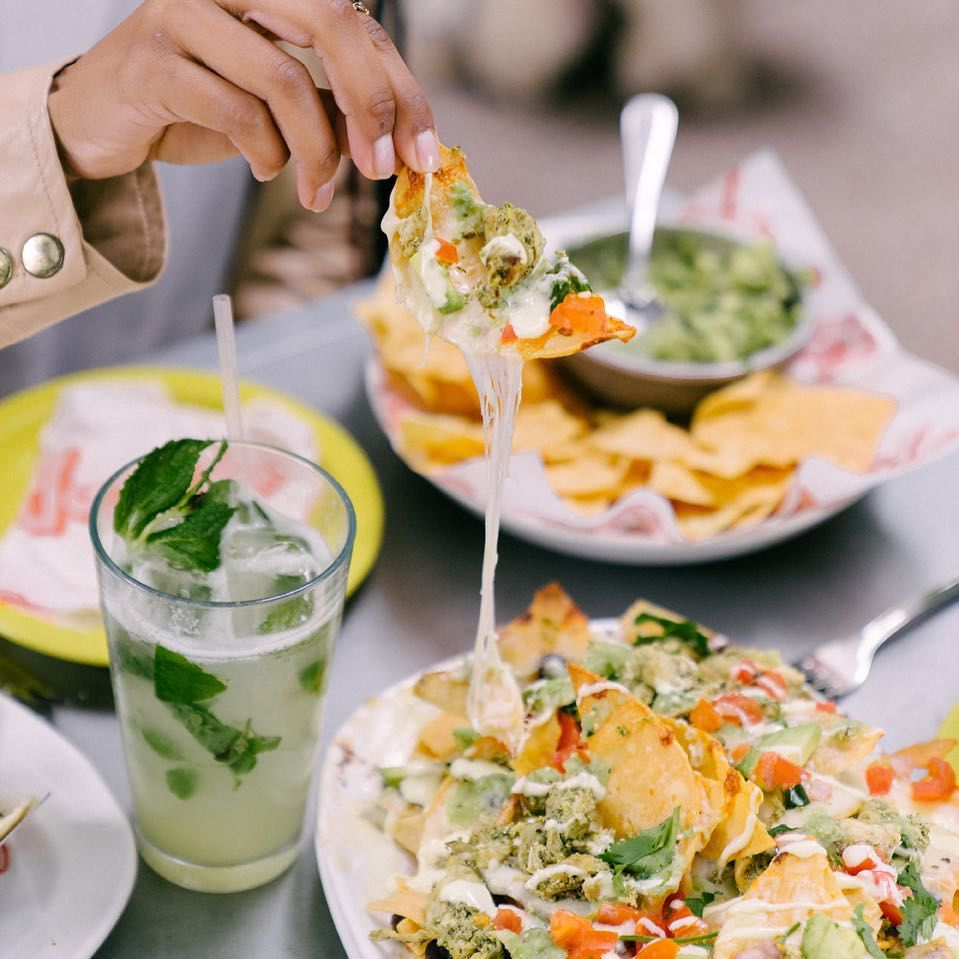 Woman's hand lifting a nacho from a plate of nachos from Joyride Taco Bar. The are tortilla chips and guacamole and a mojito also on the table