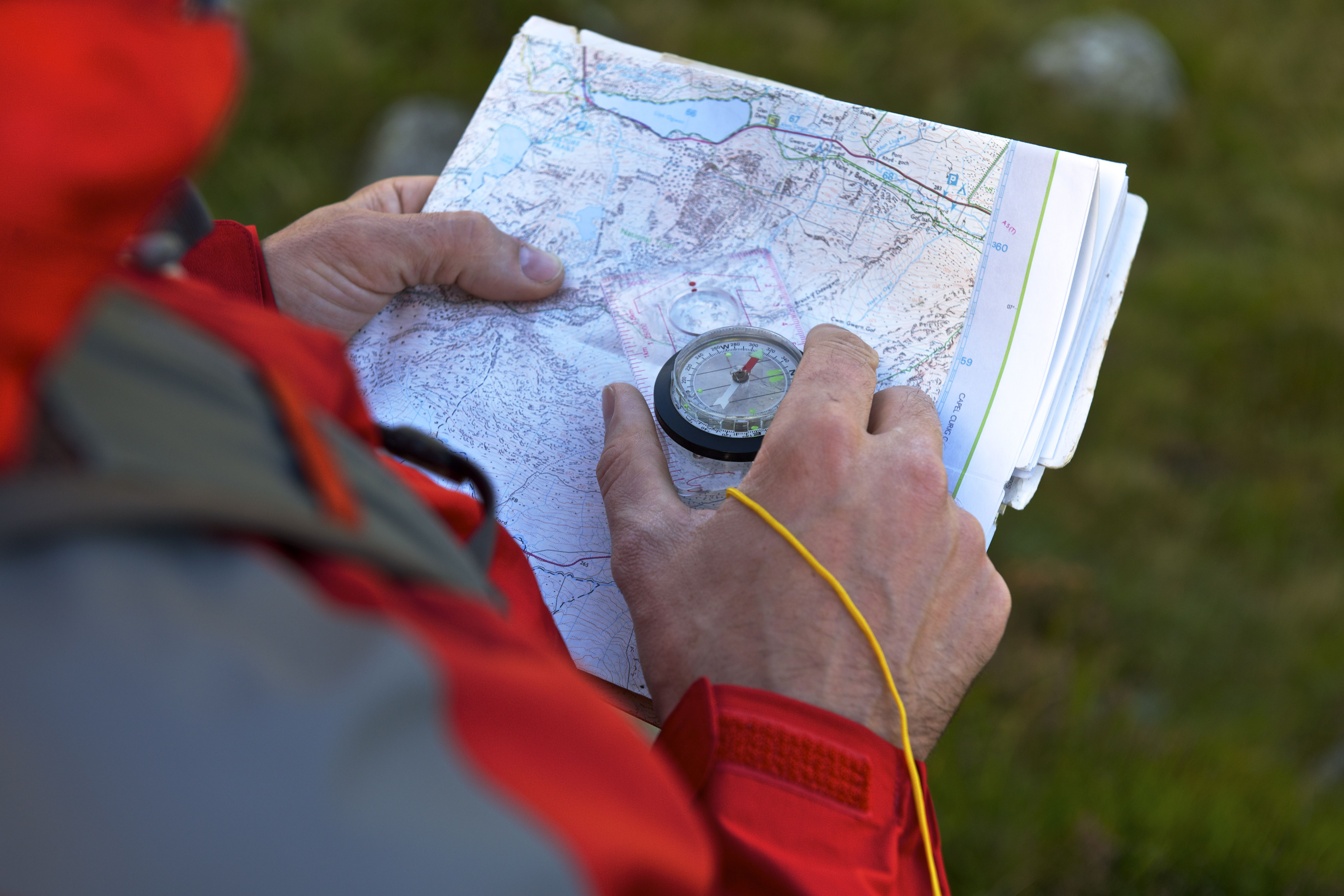 Male hiker holding compass and map