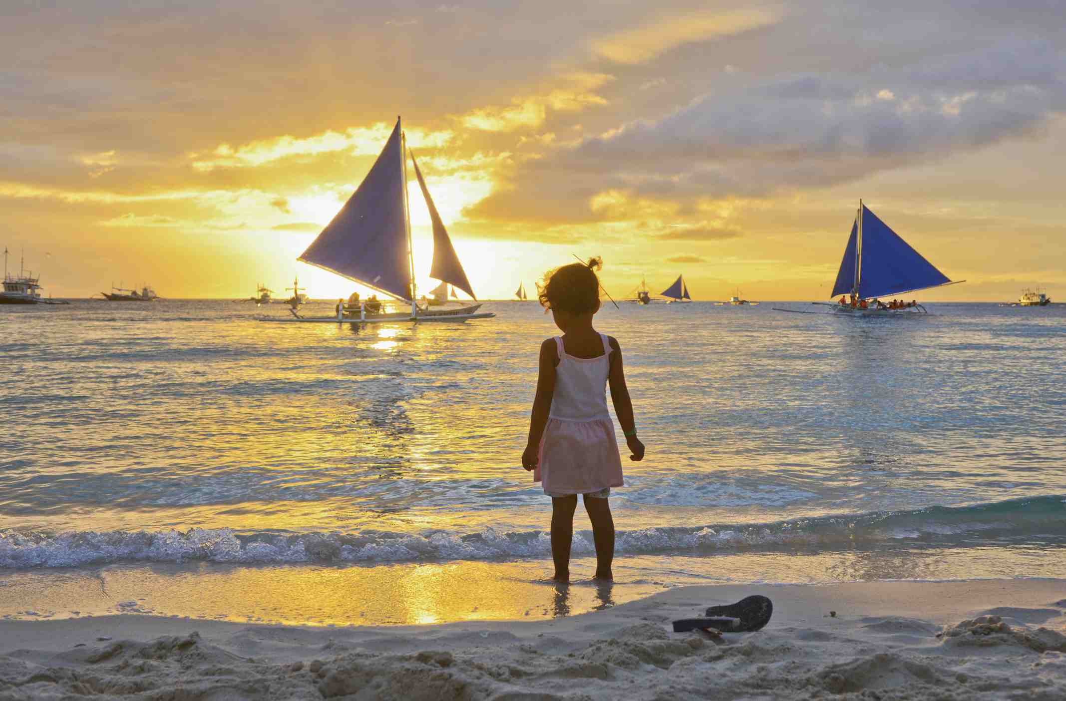 Child watching the sun set on White Beach in Boracay, Philippines