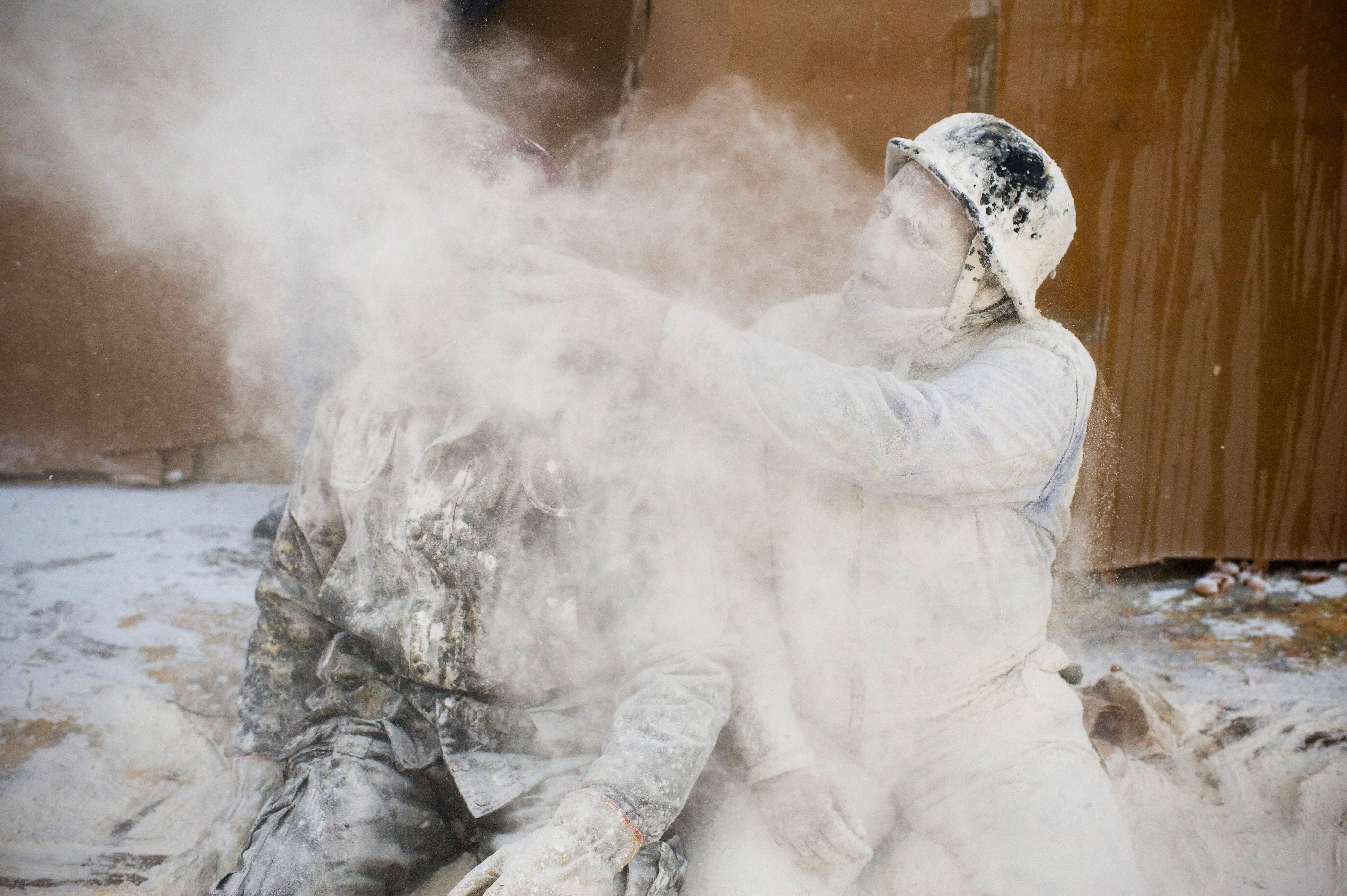 A man throwing flour at a another person during Els Enfarinats