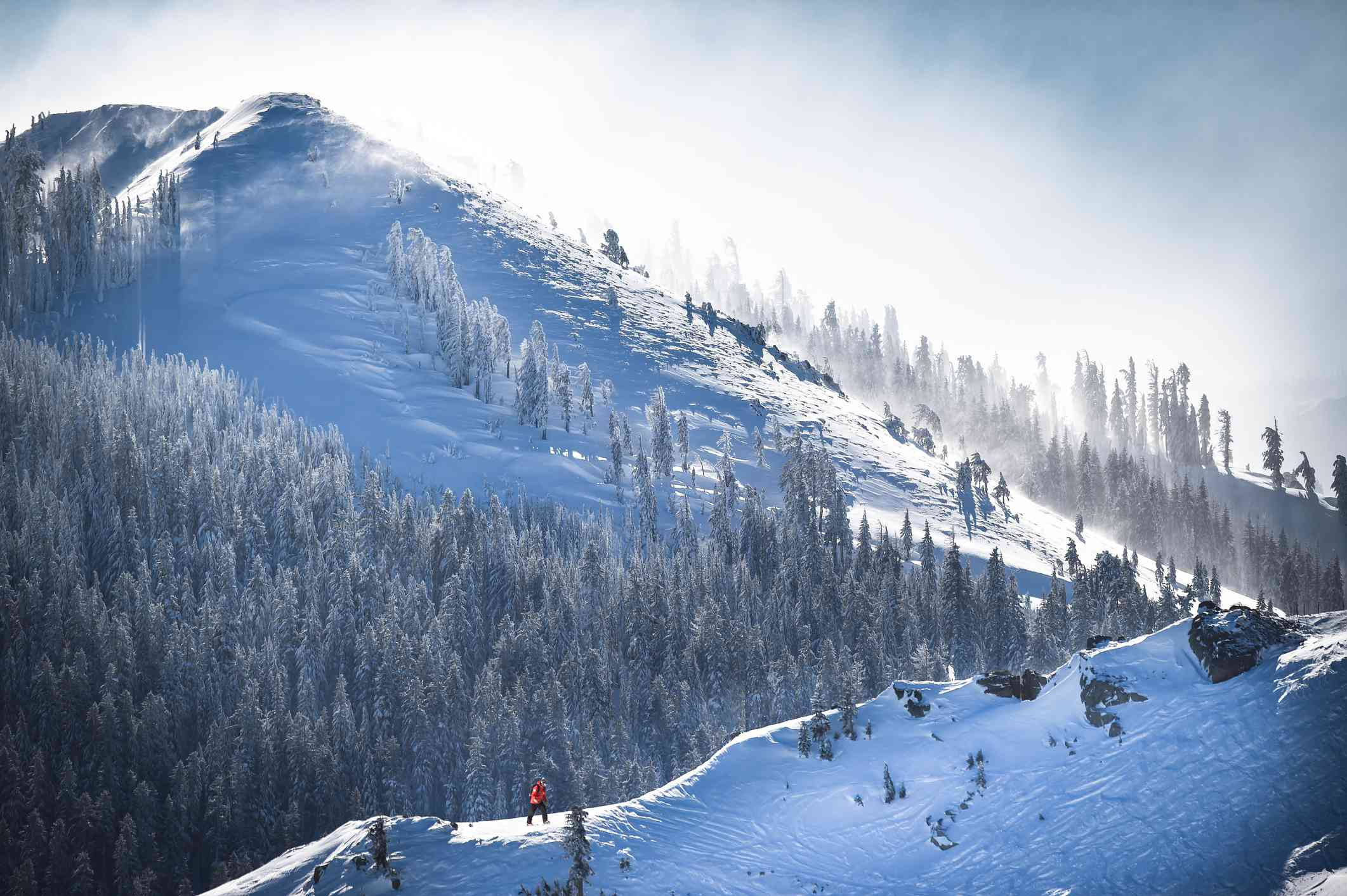 Rescue worker traverses a snowy edge of a mountain. Digital composite.