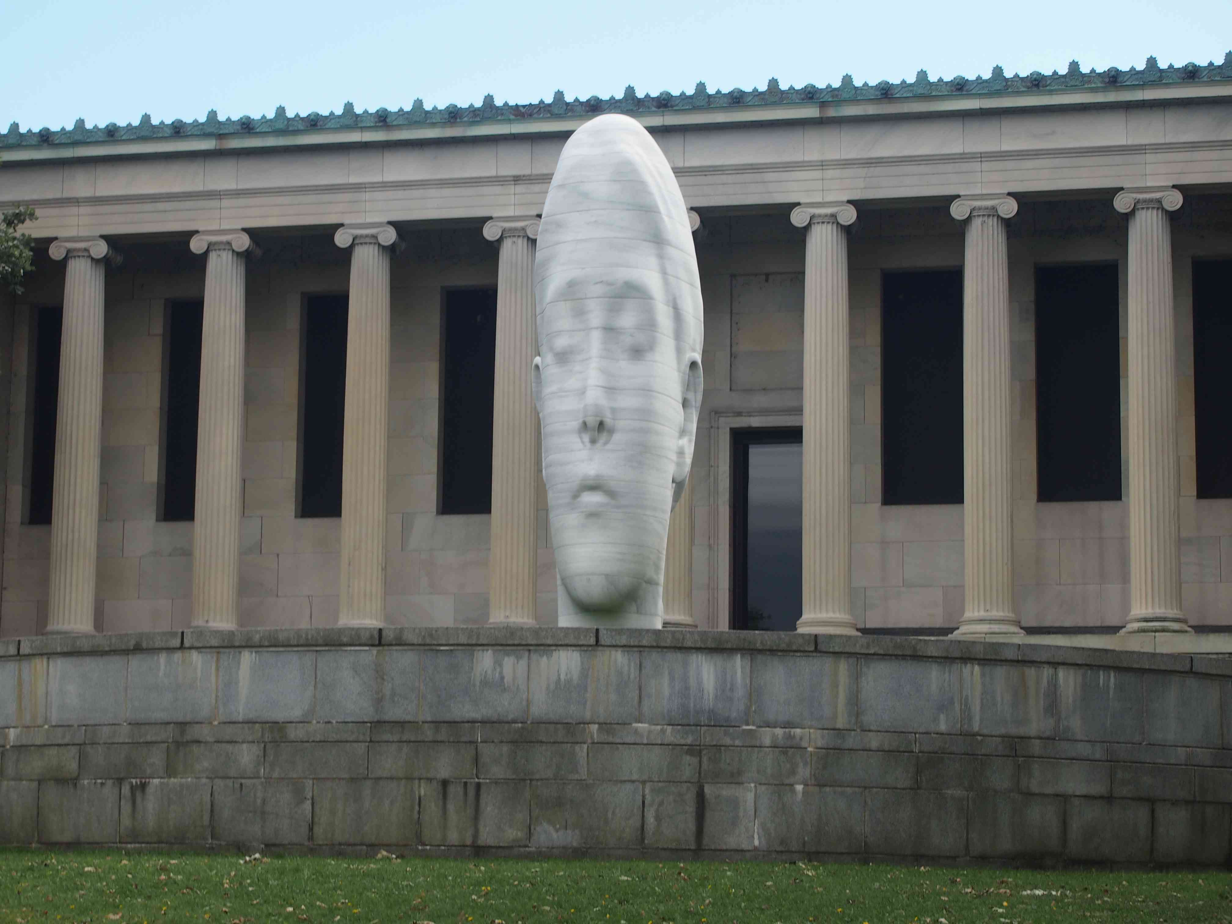 building with a row of classical columns with a white head sculpture in foreground