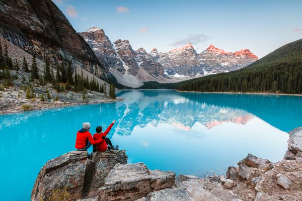 two people in red coats sitting on a rock looking at an alpine lake in Banff National Park