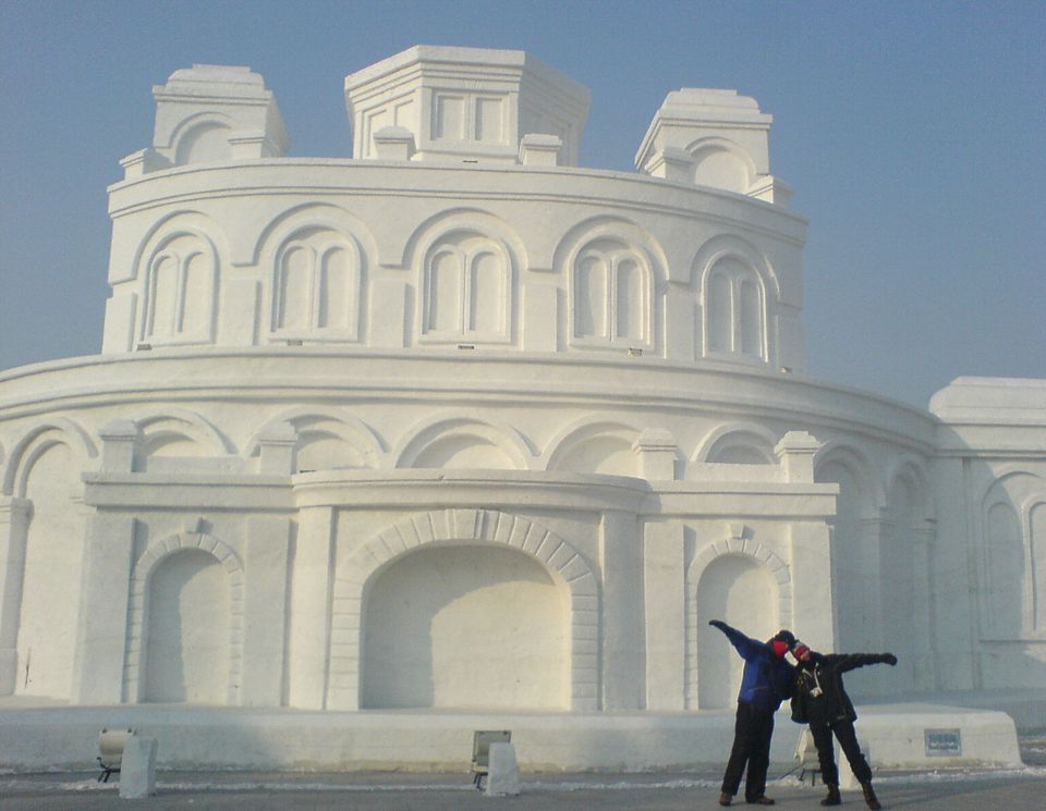 Tourists pose in front of a snow sculpture in Harbin