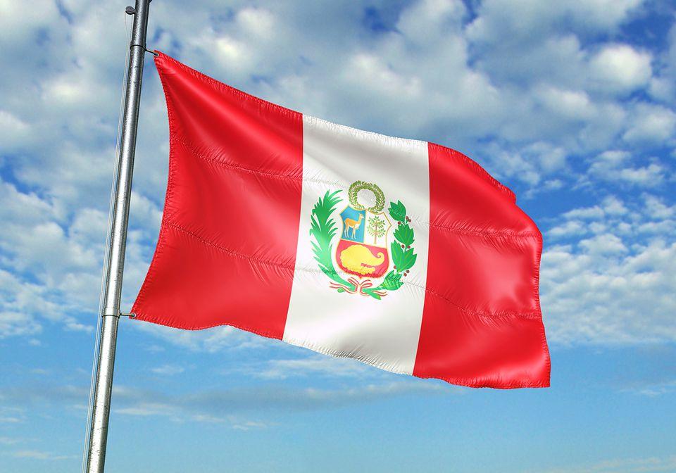 Bandera de Perú ondeando fondo de cielo nublado