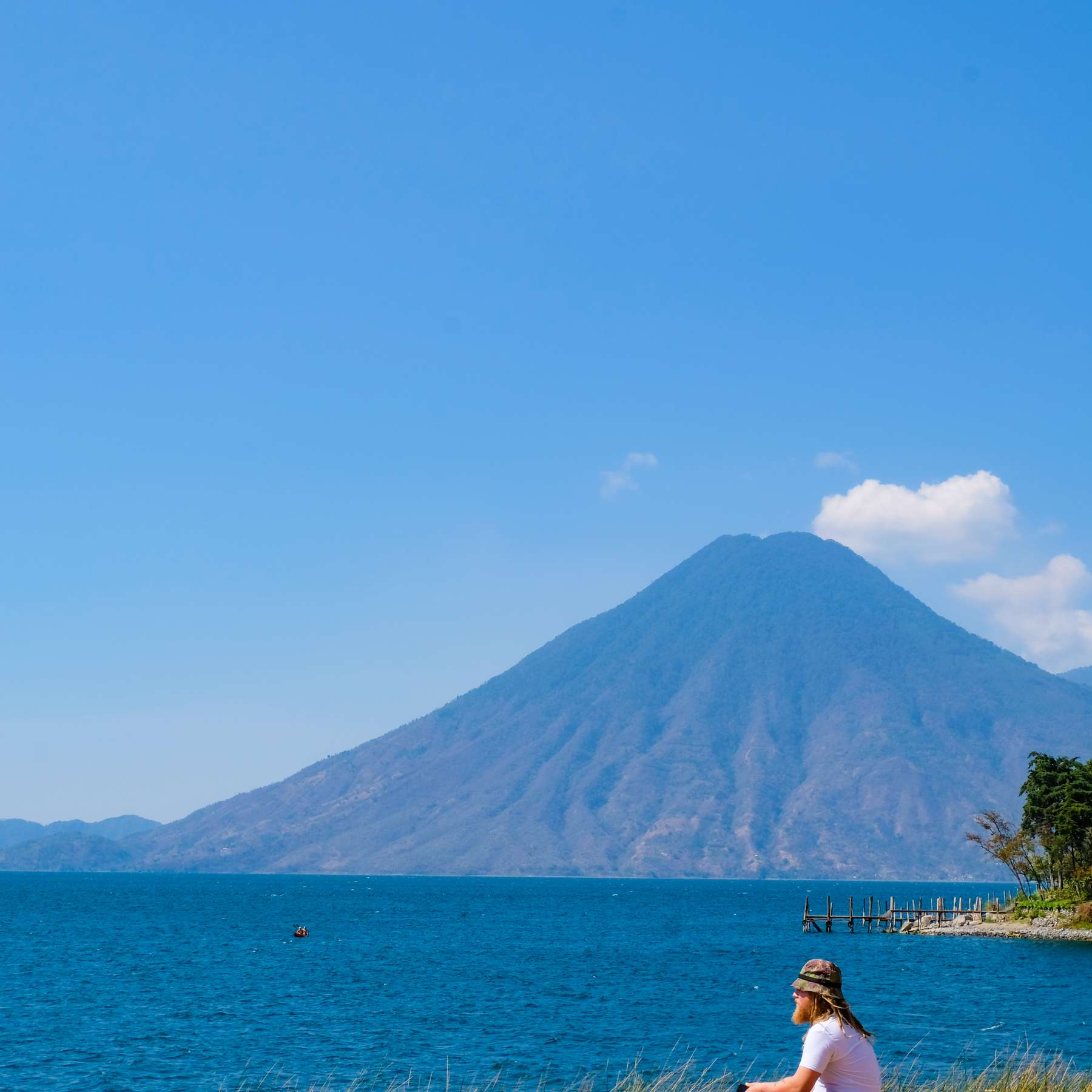 A person sitting on the coast of Lake Atitlan with a volcano in the background