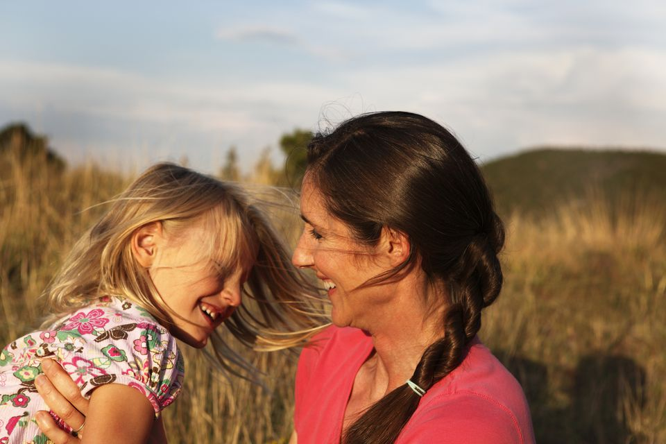 Mother smiling and playing with daughter in field