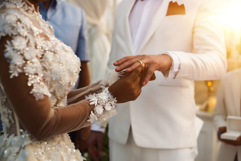 Midsection Of Bride Putting Ring In Groom Finger At Ceremony