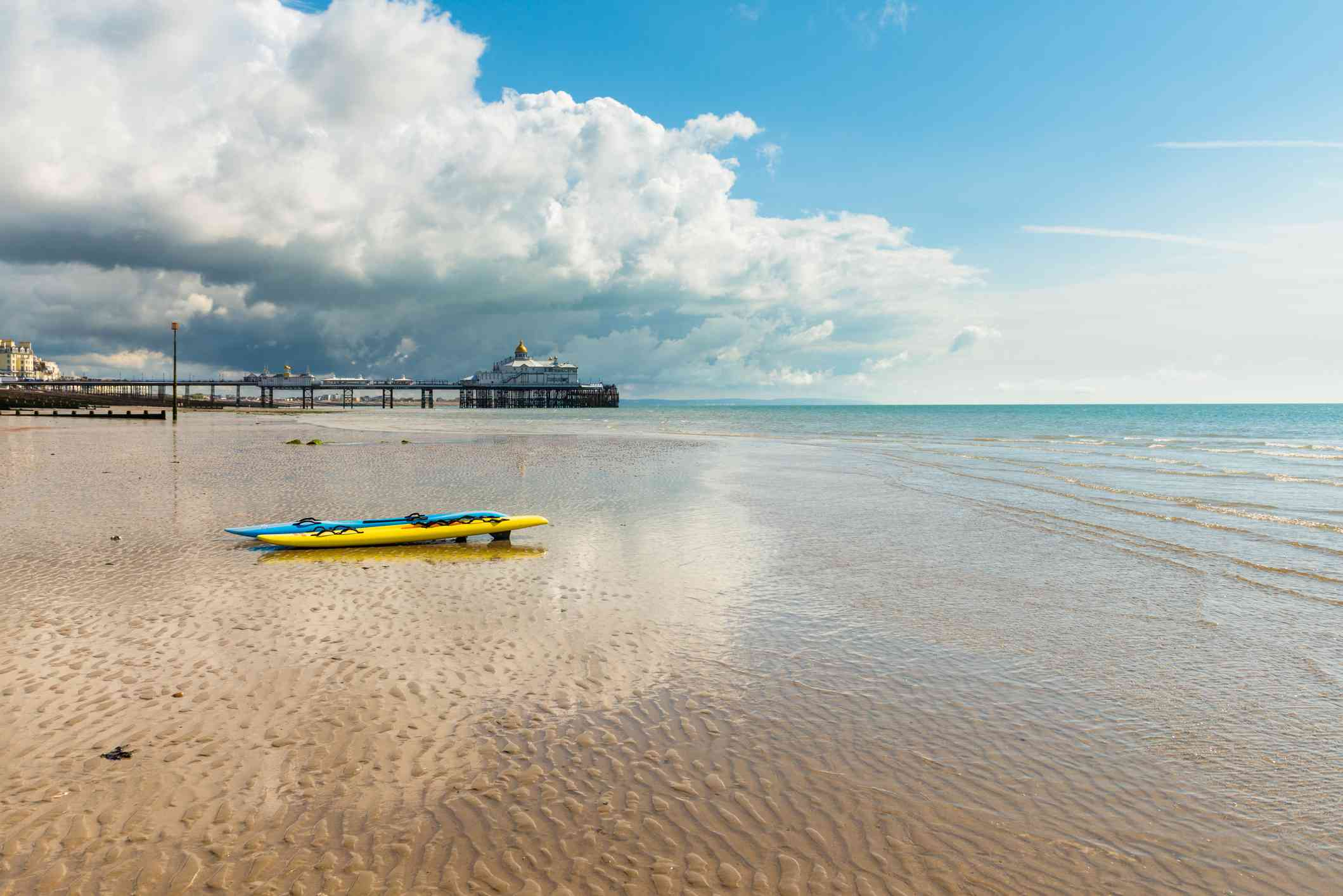 Two Kayaks on the Beach and Eastbourne Pier at Low Tide
