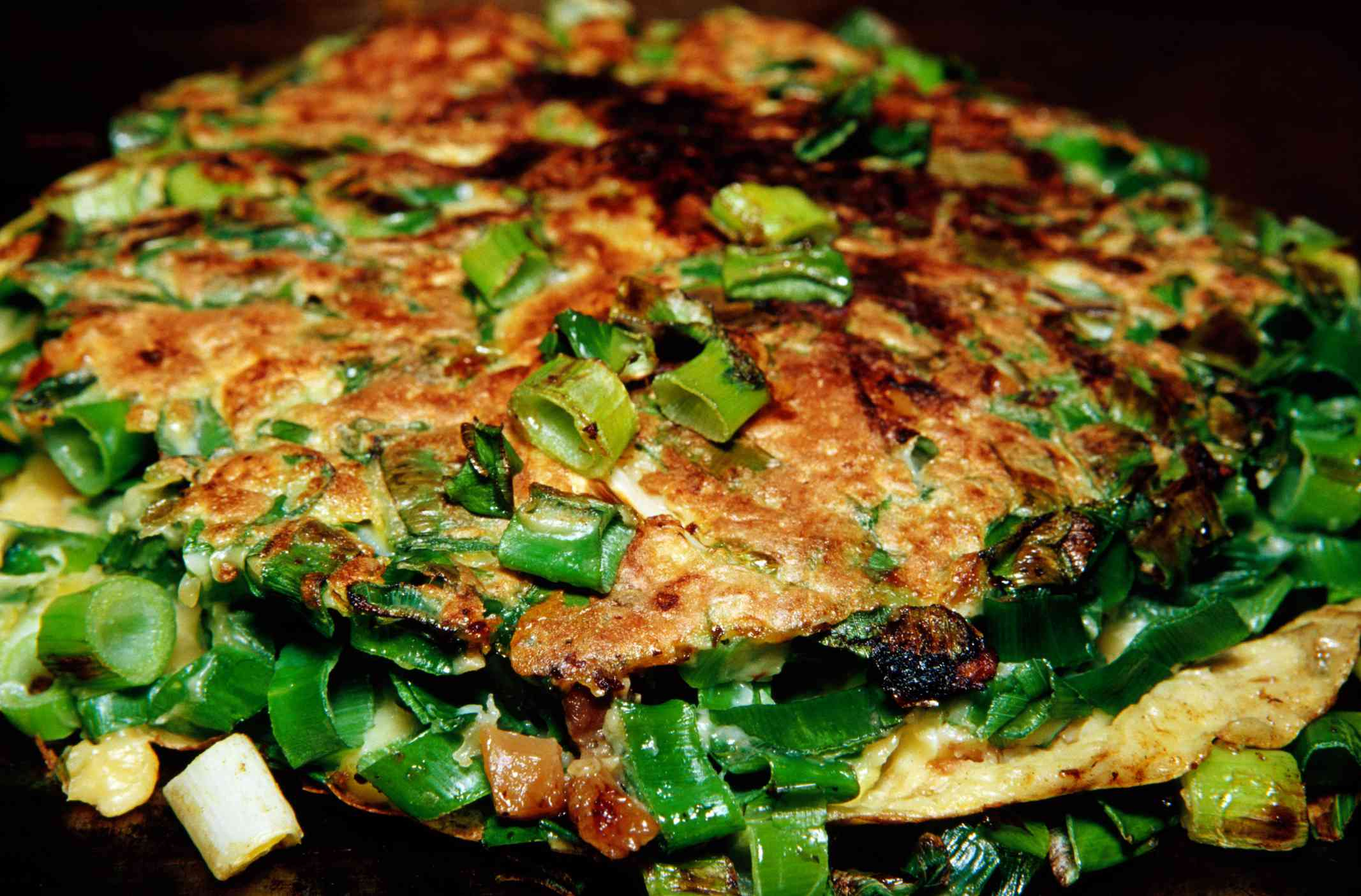 Fried scallion pancakes with additional scallions as a garnish