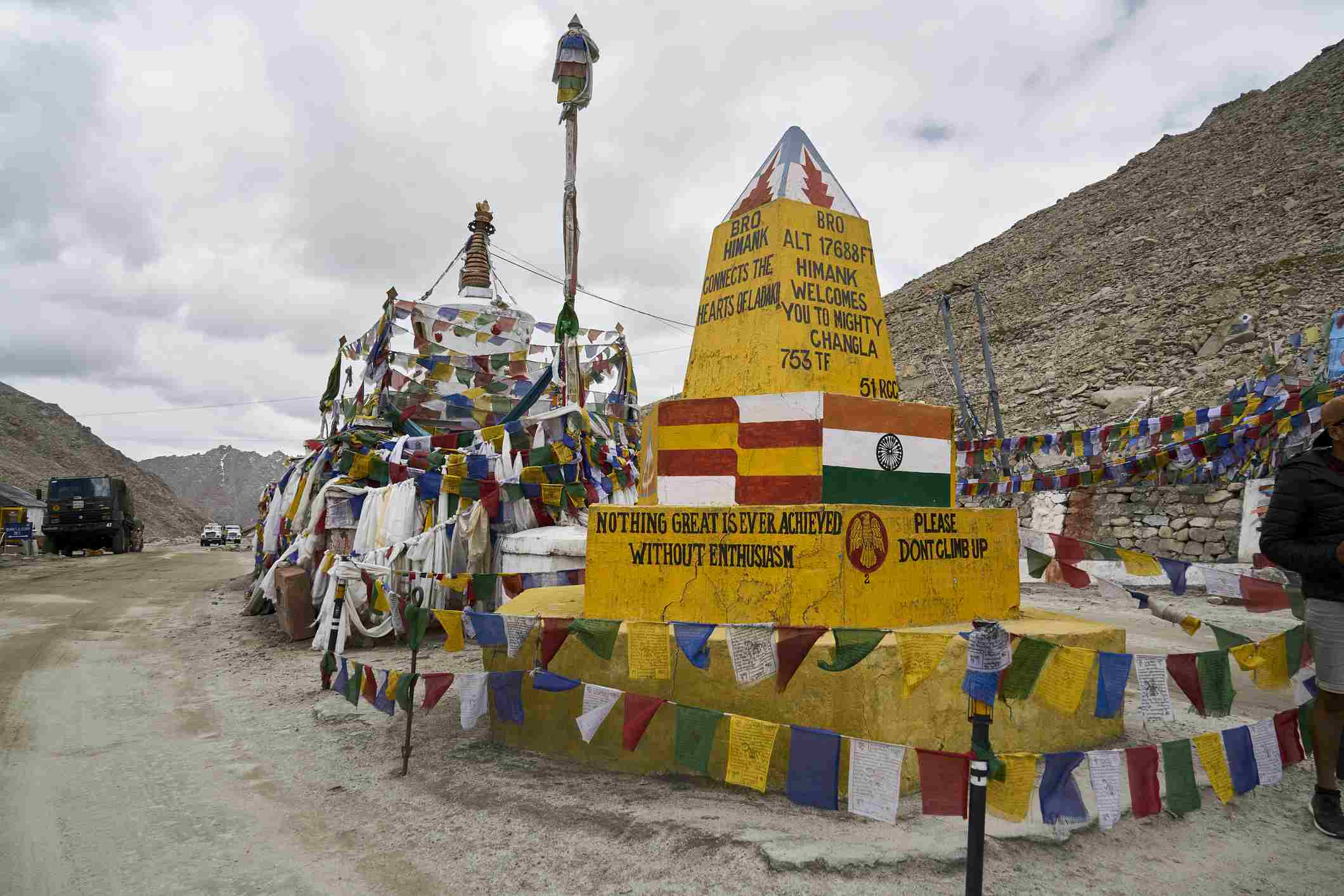 The yellow sign board and prayer flags at the Chang La Pass in Ladakh, India