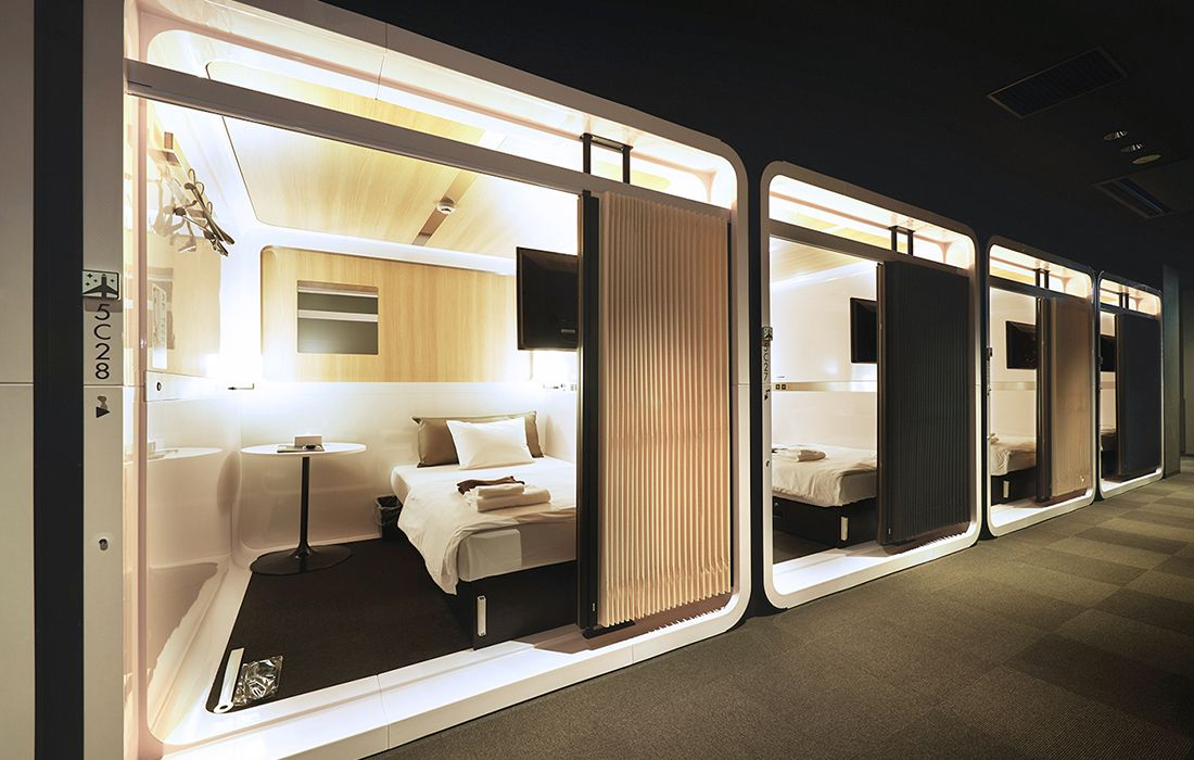four pod-style hotel rooms in a row with a bed and side table inside