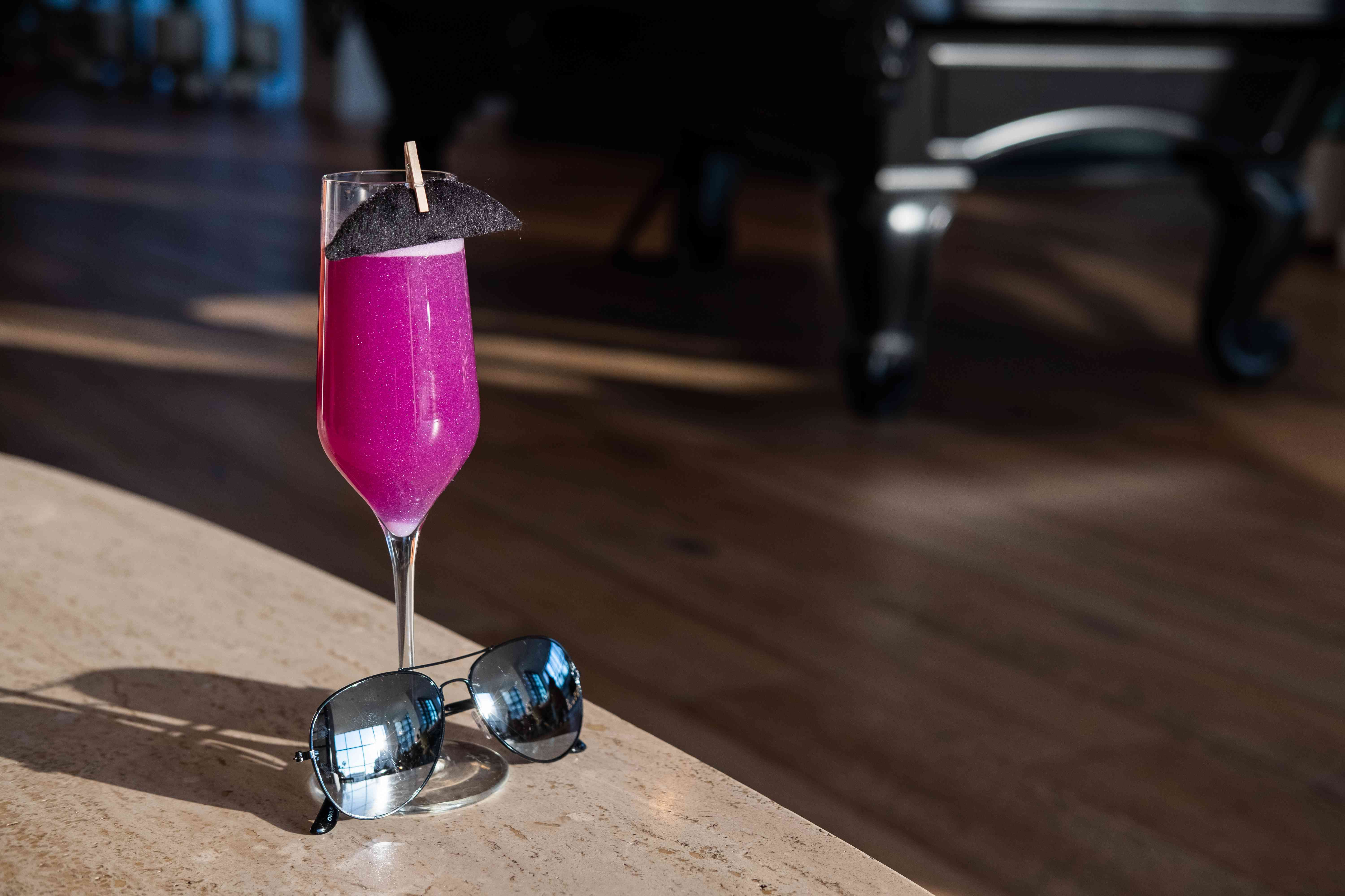 Fuschia colors drink in a champagne flute with a fake mustache clipped to the rim and a pair of aviator sunglasses at the base