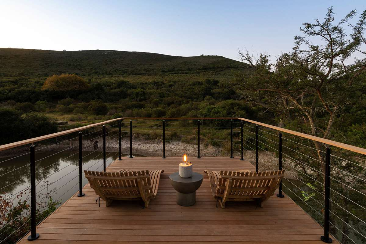 Two lounge chairs on a fenced deck overlooking Shamwari Game Reserve