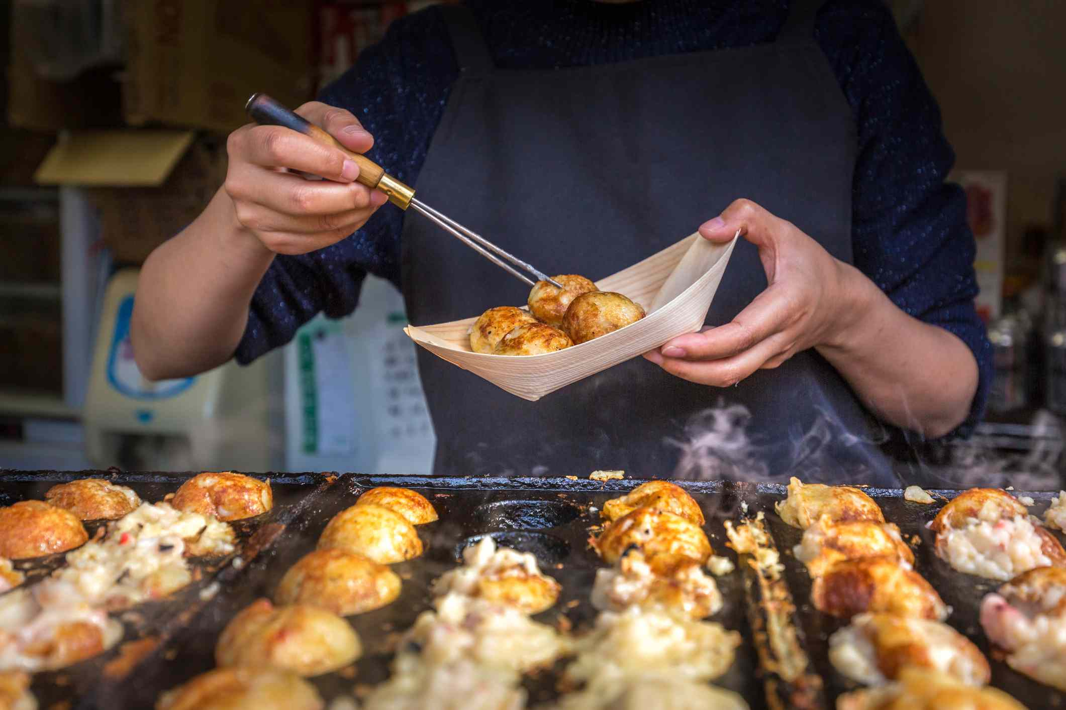 Person standing behind metal tray of cooking takoyaki while placing a takoyaki in