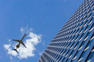 Plane by skyscraper