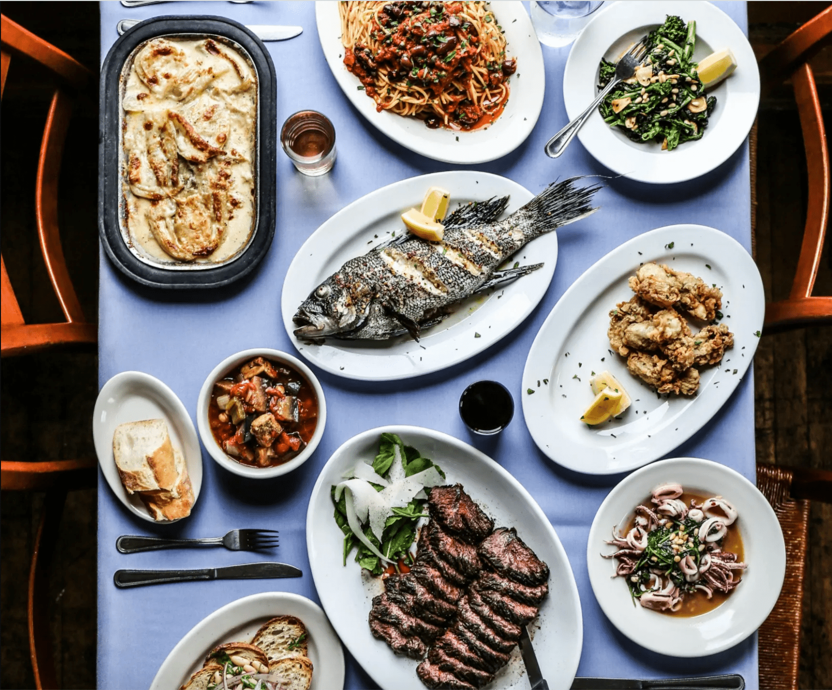 Blue table filled with italian entrees like a whole grilled fish and sliced hangar steak